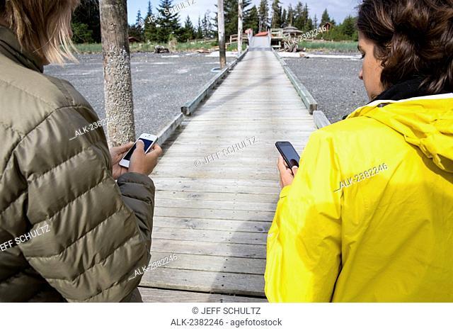 Women in rain gear using smart phone at Tutka Bay Lodge, Alaska, Summer