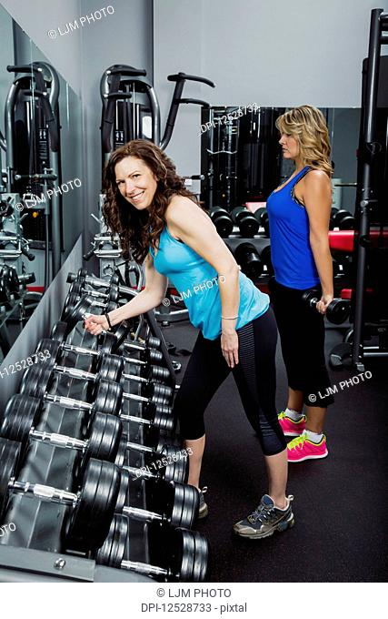 Two attractive middle-aged women working out at a fitness facility using free weights; Spruce Grove, Alberta, Canada