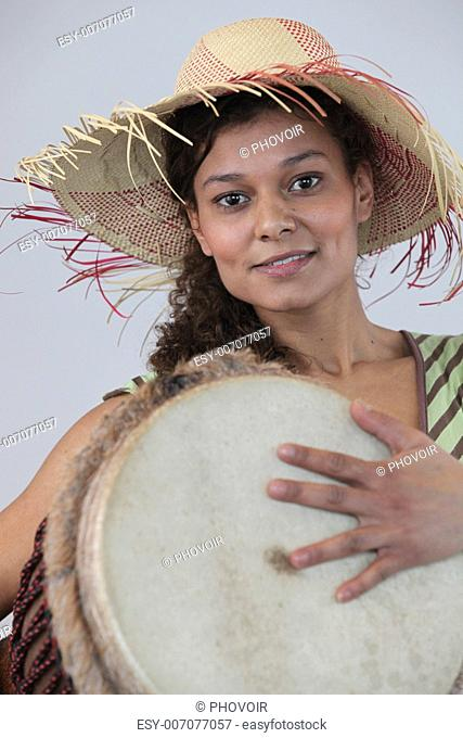 Woman wearing a straw hat and playing the djembe
