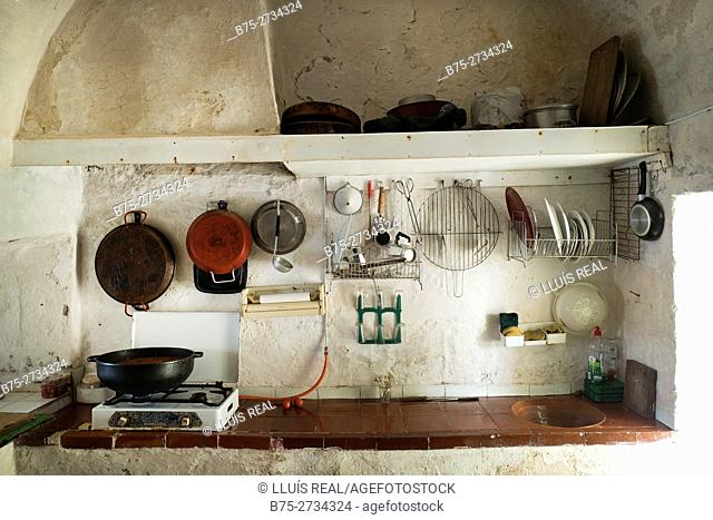 Old and simple kitchen in a fishing lodge with cooking utensils, gas cooker, pots, dishes, etc. Sa Mesquida, Mahó, Minorca, Balearic Islands, Spain