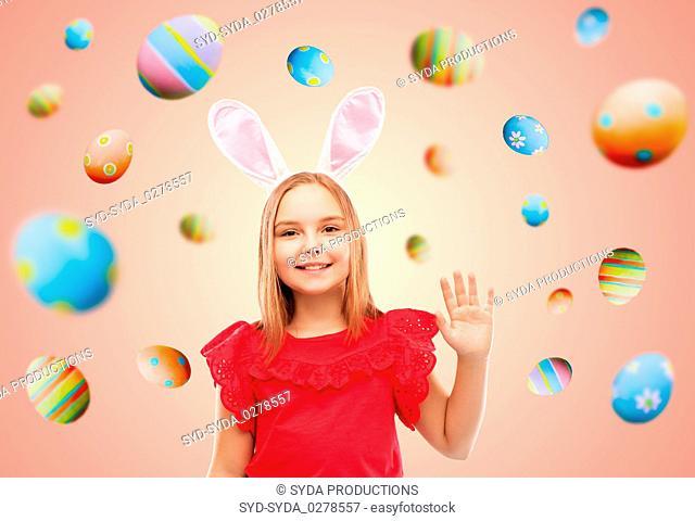 happy girl wearing easter bunny ears waving hand