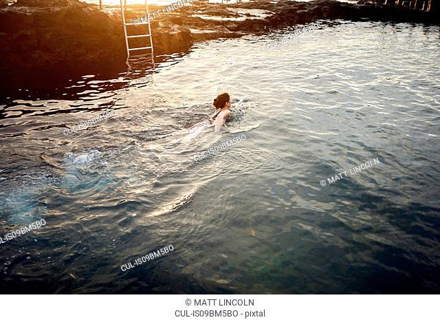 Woman swimming in coastal pool at sunset, Las Palmas, Gran Canaria, Canary Islands, Spain