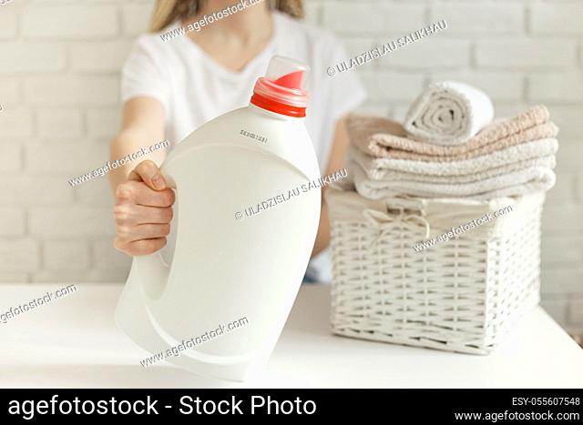 Woman holding white bottle with detergent. Wicker basket with clothes and on table