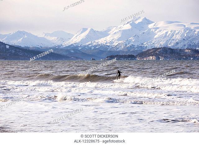 Surfer in Kachemak Bay, South-central Alaska; Homer, Alaska, United States of America