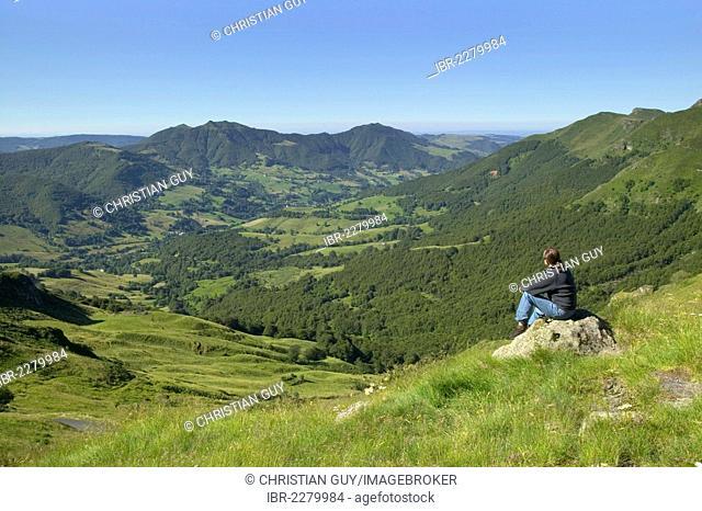 Hiker overlooking Mandailles Valley, Parc Naturel Regional des Volcans d'Auvergne, Auvergne Volcanoes Regional Nature Park, Cantal, France, Europe