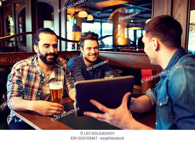 people, leisure, friendship, technology and bachelor party concept - happy male friends with tablet pc computer drinking beer at bar or pub
