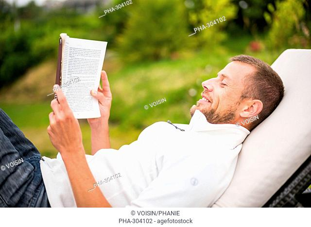 Man reading a book in lounge chair outdoor