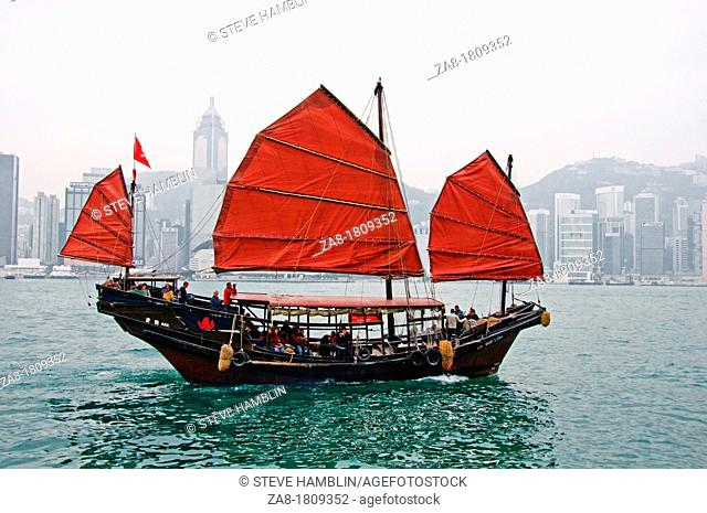 Colorful Chinese junk with red sail in Hong Kong Victoria harbor