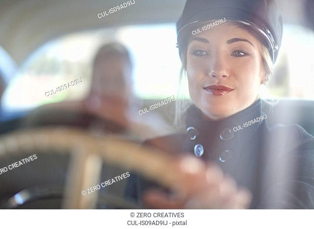 Woman playing chauffeur in vintage car
