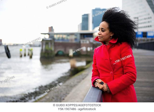 Rotterdam, Netherlands. Young, African woman with a red winter coat, pondering and looking out over the river, next to the Willemsbrug in Rotterdam