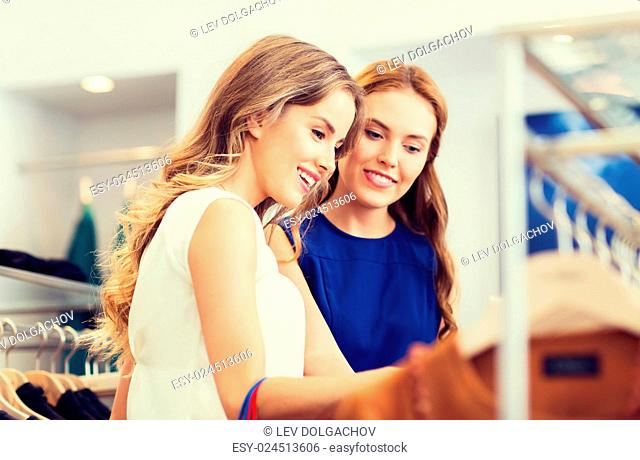 sale, shopping, consumerism and people concept - happy young women choosing clothes at clothing shop