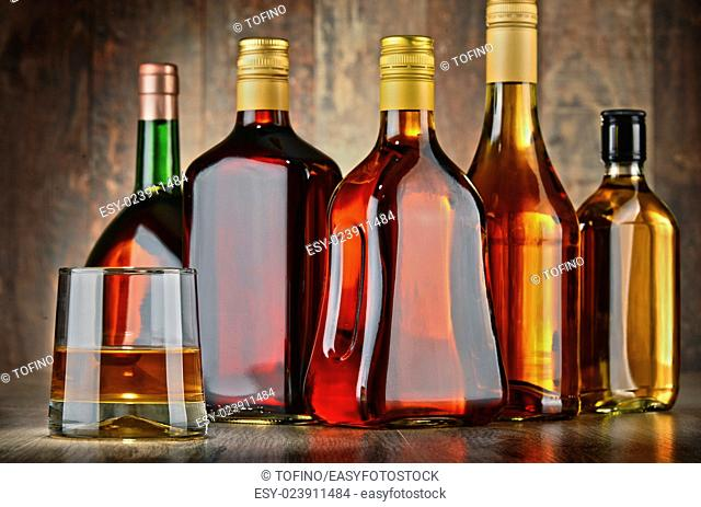 Glass and bottles of assorted alcoholic beverages