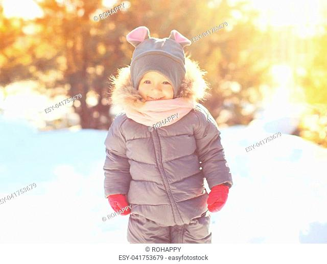 Winter portrait happy smiling little child playing in sunny day