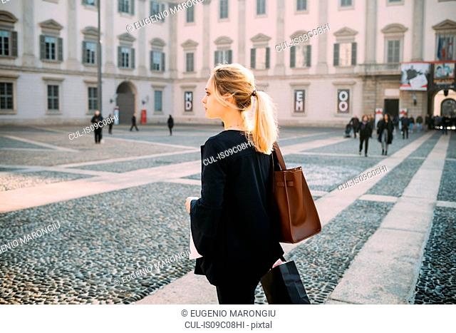 Young female tourist with shopping bags in city square, Milan, Italy
