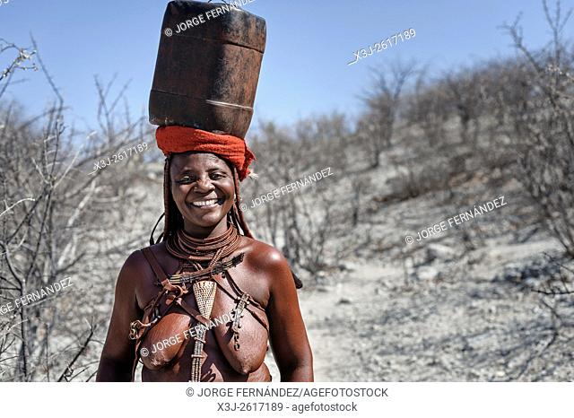 Himba woman carrying a plastic container full of water on her head smiling at the camera
