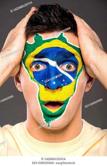 Portrait of young man with brazilian flag painted on his face