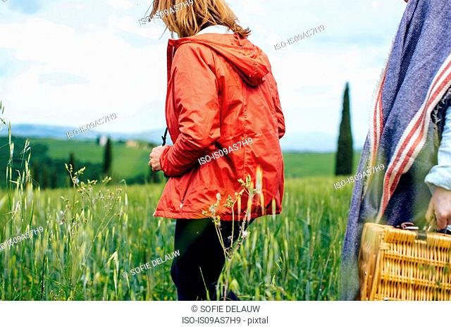 Cropped shot of two mature women strolling in wheatfield, Tuscany, Italy