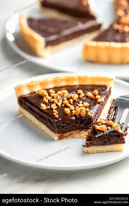 Sweet chocolate pie with crushed nuts on plate