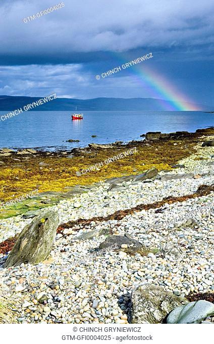 Rainbow above Fishing Boat on Rocky Shore