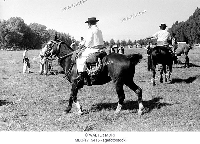 Gauchos on horseback. Two gauchos on horseback in the pampa, they are the typical South America cattlemen, the equivalent of North American cowboys