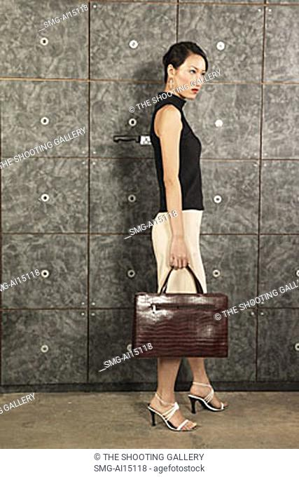 Female executive carrying briefcase, knife sticking out of her back