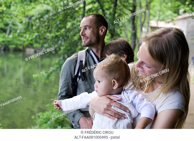 Family in woods, focus on mother holding baby girl