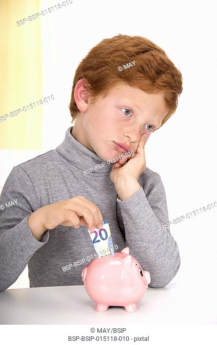 Boy putting banknote to piggybank