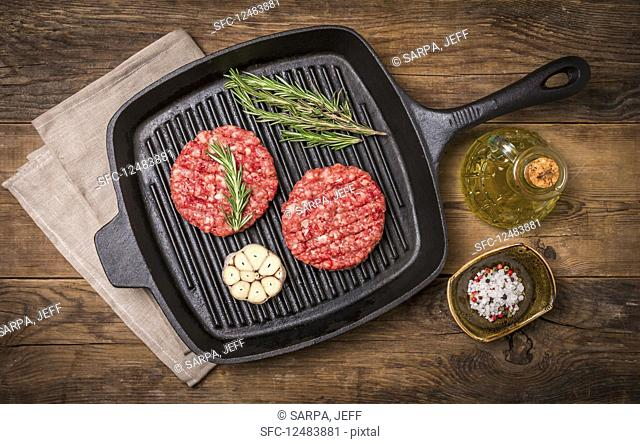 Raw burgers from organic beef with garlic and rosemary in a frying pan on an old wooden table, top view