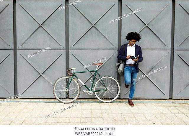 Businessman with bicycle leaning against a wall reading book