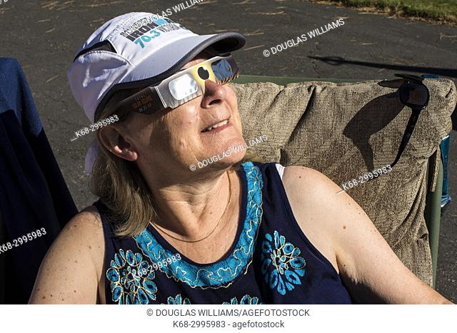 Woman looking at solar eclipse with protective glasses