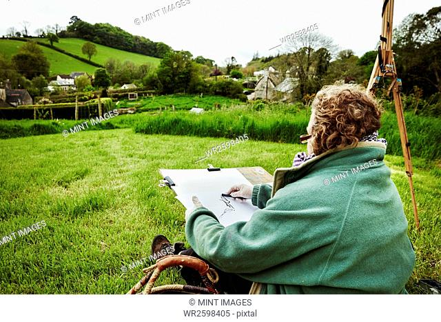 A woman artist sketching with charcoal on paper, sitting on the ground outdoors