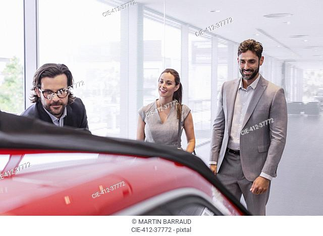 Car salesman showing new car to couple customers in car dealership showroom