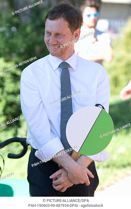 03 June 2019, Saxony, Dresden: Michael Kretschmer (CDU), Prime Minister of Saxony, holds a starter flap on the occasion of the start of the summer cycle tour...