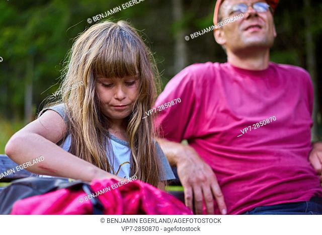 Young girl is taking a rest with her father during hiking adventure