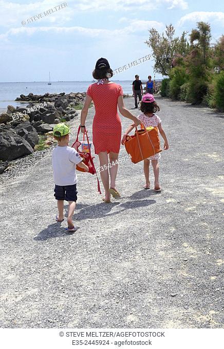 A well dressed mother takes her children to the beach