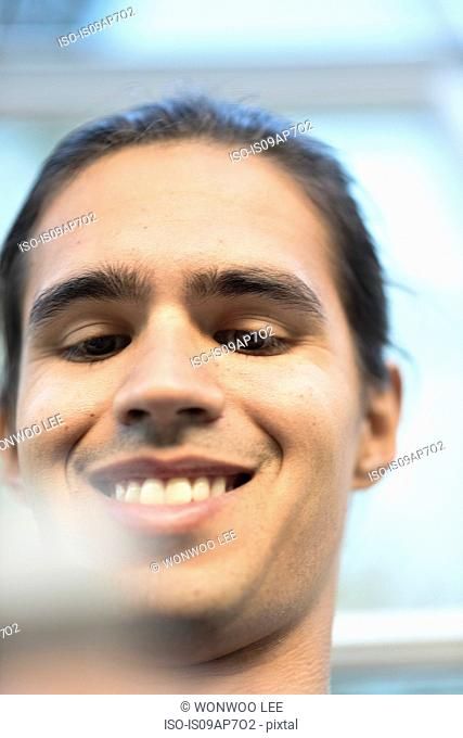 Young man, smiling, low angle view