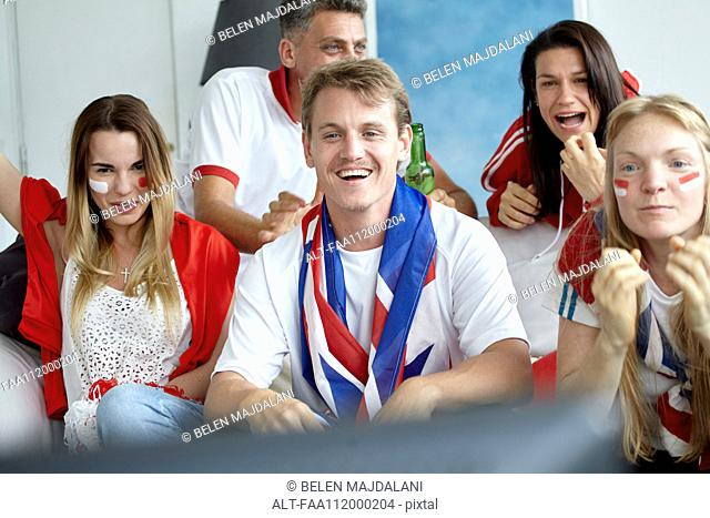 British football fans watching match on TV at home