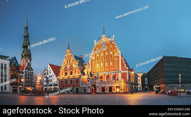 Riga, Latvia. Panorama Of Town Hall Square With St. Peter's Church, Schwabe House, House Of Blackheads. Famous Landmarks In Summer Evening Or Night At Blue Hour