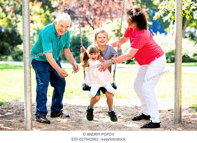 Senior Grandparents Having Fun With Kids On Swing In The Park