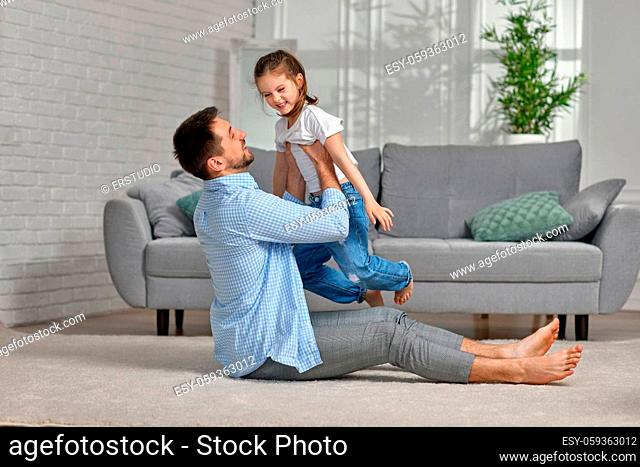 handsome father playing with excited happy little child girl at home