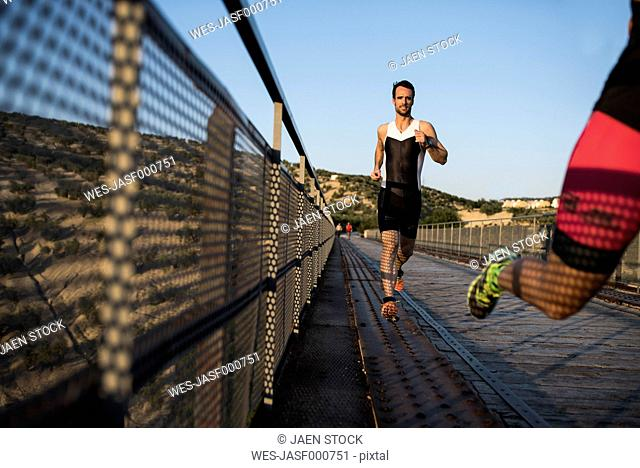 Two athletes running on a bridge