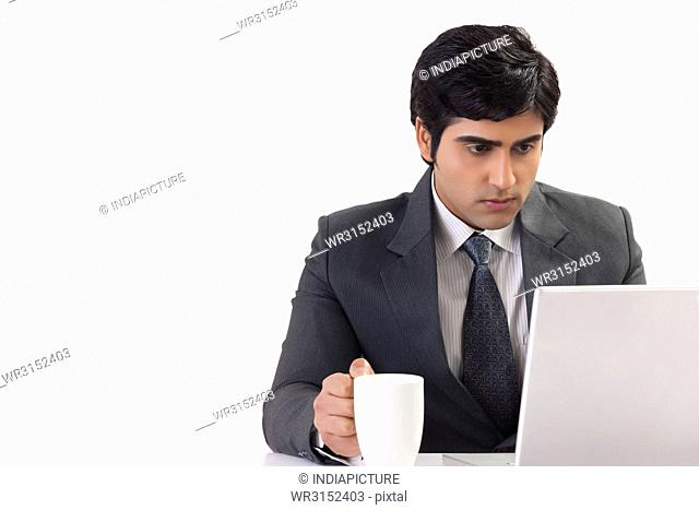Businessman holding coffee cup working on desk at office