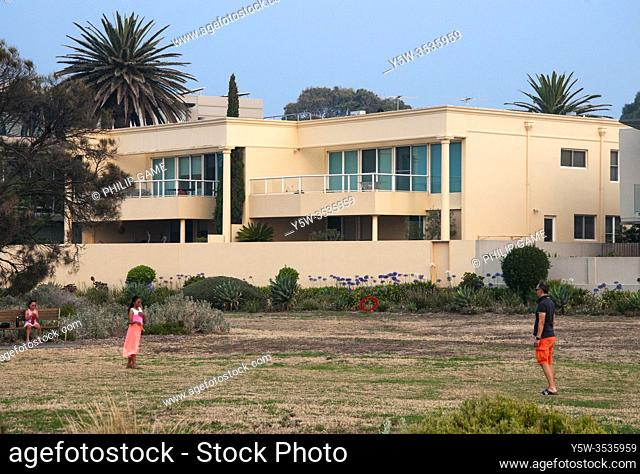 Children play outside a luxury seaside mansion in the 'Golden Mile' at Brighton Beach, Melbourne, Australia