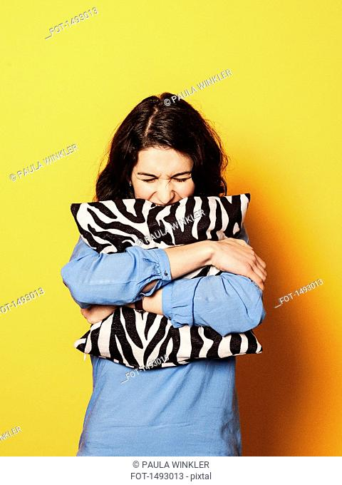 Irritated young woman embracing cushion against yellow background