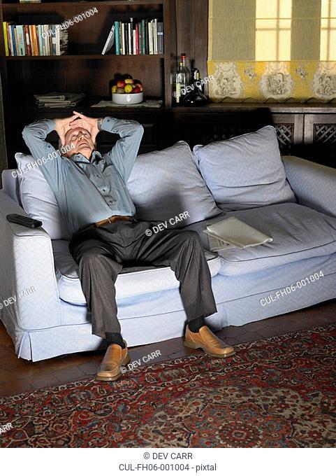 Senior man holding forehead sitting on sofa illuminated by television