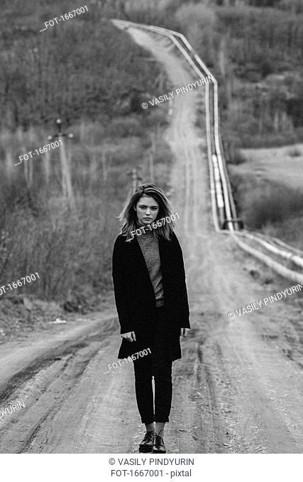 Full length of teenage girl standing on dirt road against trees