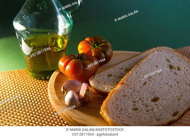 Still life: oil bottle, garlic, tomatoes and bread. Close view