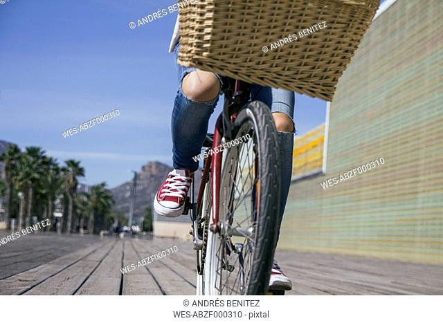 Young woman riding bicycle with basket, low section