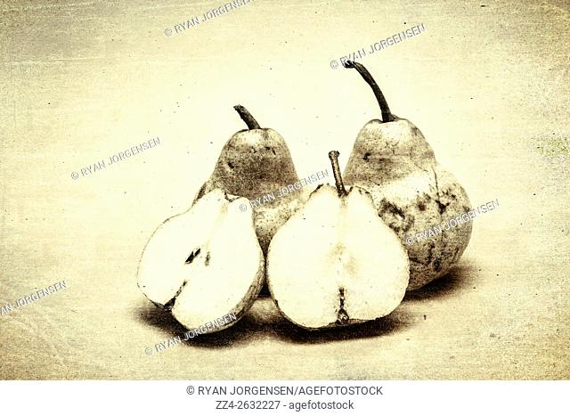 Close-up vintage still of three ripe pears. One of them halved