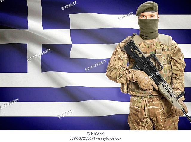 Soldier holding machine gun with national flag on background - Greece